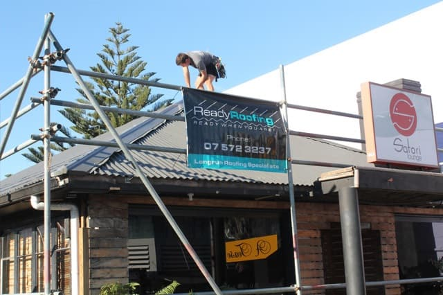 Roof repairs on a small commercial building using long run roofing