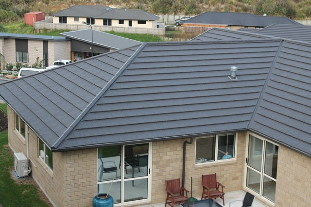 Grey concrete roofing product used on a small modern home with beige brick